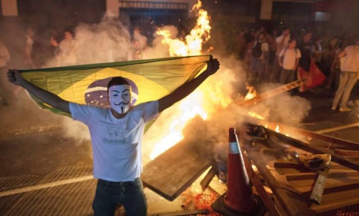 Em Niterói, manifestante com a máscara de Guy Fawkes exibe a bandeira brasileira CHRISTOPHE SIMON / AFP