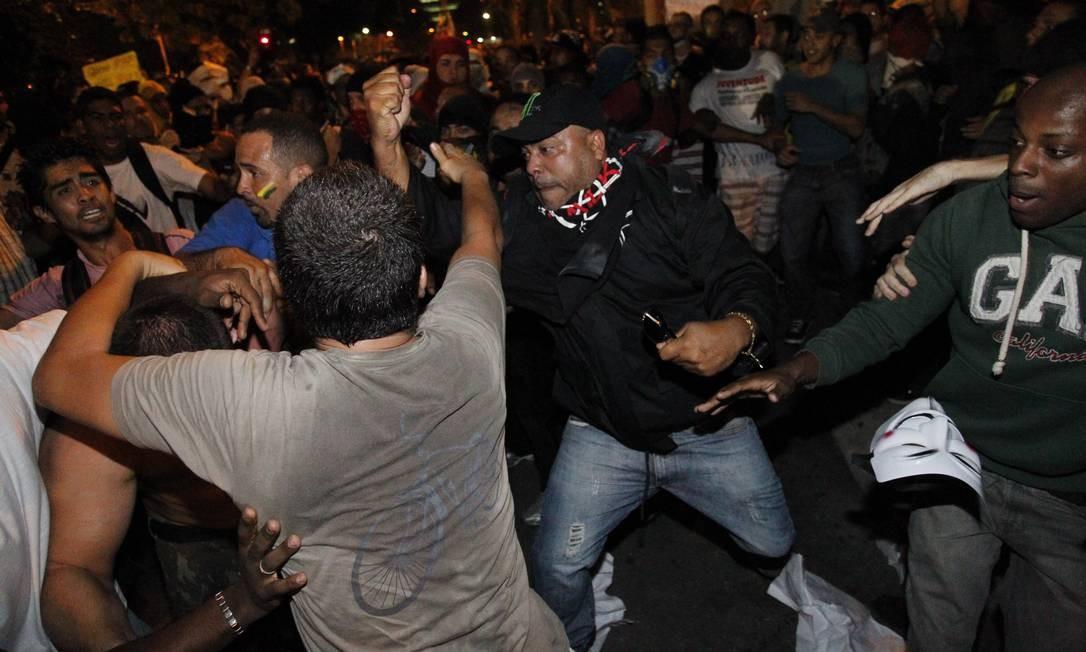 Os policiais chegaram a avançar com carros para cima dos manifestantes. Um pequeno grupo de pessoas usou tapumes para se proteger e avançar em direção aos policiais, que tentaram se proteger atrás de mureta Foto: Agência O Globo