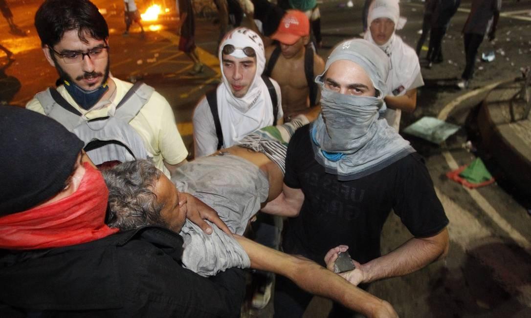 Homem é socorrido após ser ferido no tumulto na Avenida Presidente Vargas Foto: Marcelo Piu / Agência O Globo