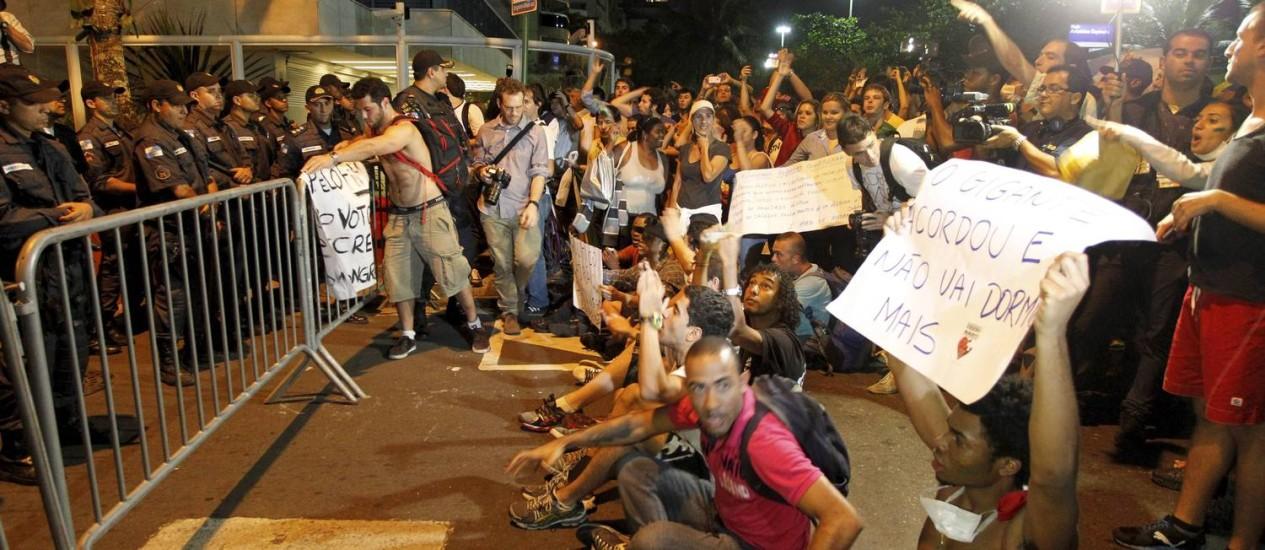 Manifestantes ficam sentados na asfalto, na esquina da Rua Aristides Espínola, no Leblon: protesto contra o governador Sérgio Cabral Foto: Domingos Peixoto / Agência O Globo