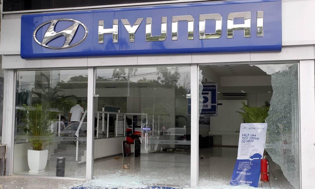 Vidraças quebradas em concessionária de automóveis que foi vandalizada, na Barra Foto: Roberto Moreyra / Extra