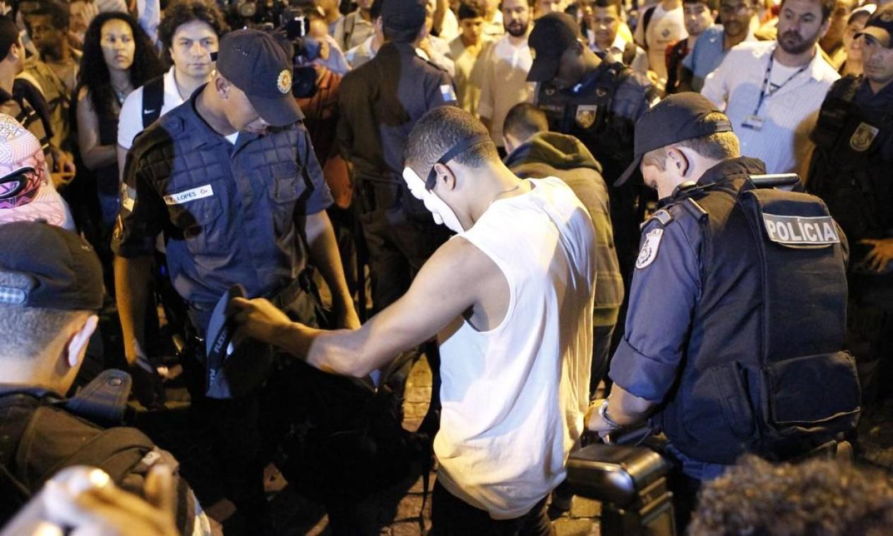 Mascarado é revistado por PM em manifestação no Centro do Rio Foto: Marcelo Piu