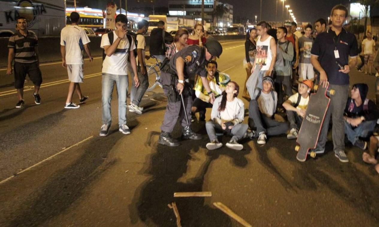 Policial fala com manifestante sentado no asfalto da Avenida Brasil Foto: Marcelo Theobald / Agência O Globo