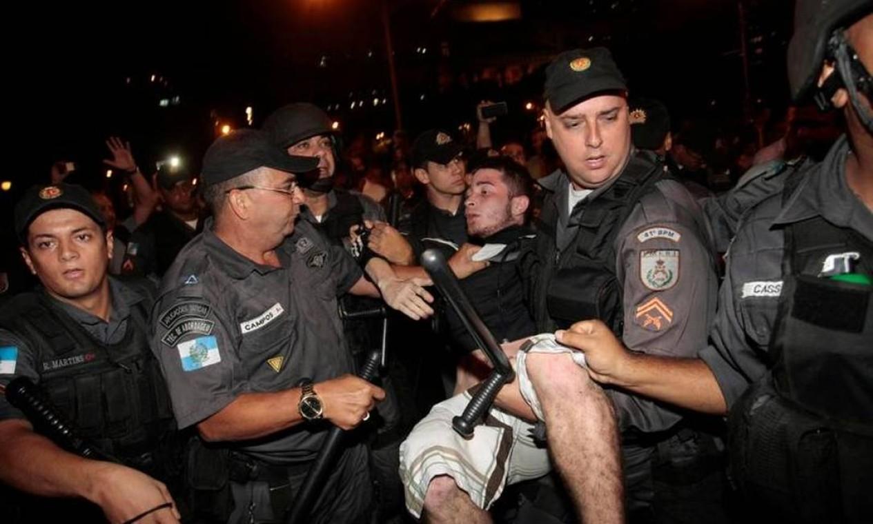 Manifestante é carregado por PMs na Cinelândia Foto: Cléber Júnior