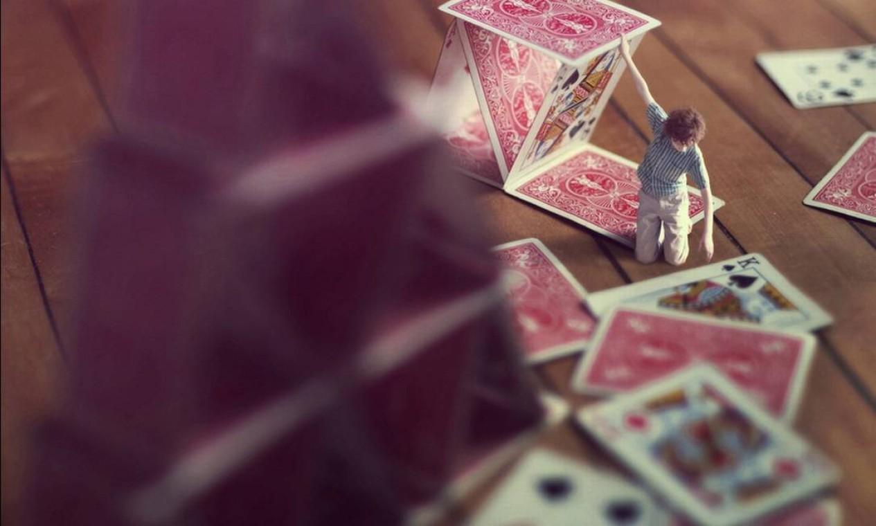 Ele conta com a ajuda da irmã Nellie, de 18 anos, para criar as imagens. Nesta, ele começa a montar uma nova torre de cartas de baralho Foto: Zev Hoover/ Fiddle Oak / Reprodução de internet