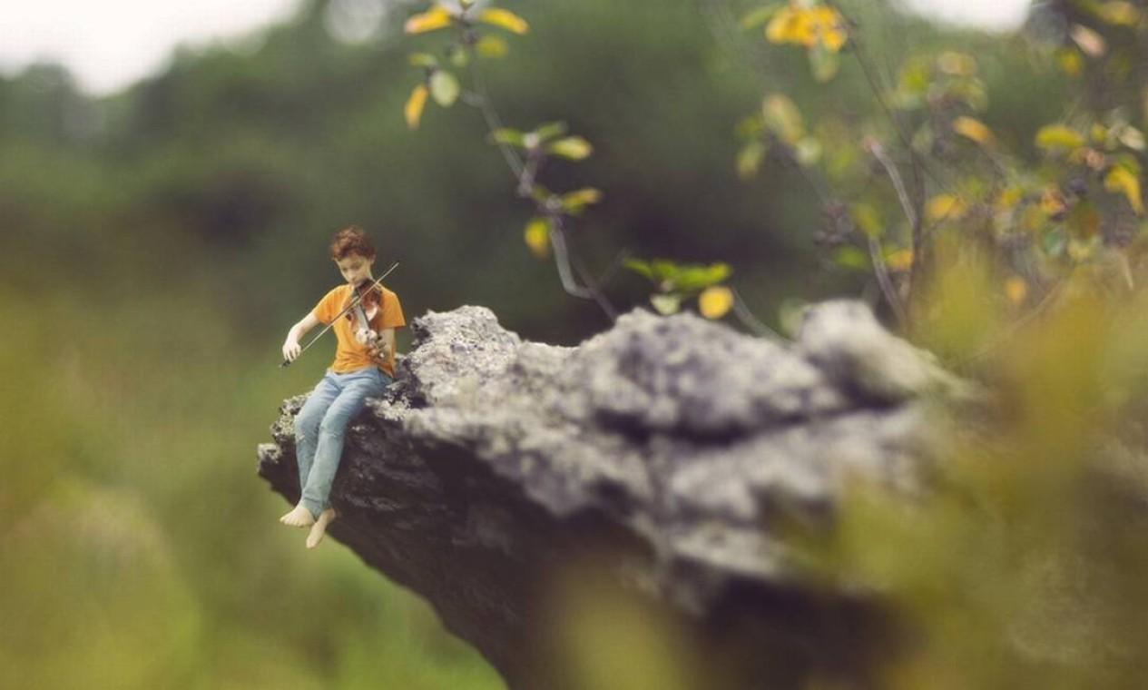 Sentado na beira de uma pedra, o rapaz toca violino Foto: Zev Hoover/ Fiddle Oak / Reprodução de internet