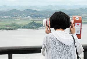 Visitantes observam a região da fronteira da Coreia do Norte, perto de Panmunjom Foto: Ahn Young-joon / AP