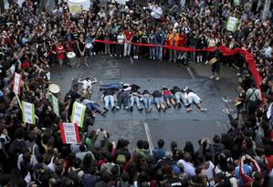 Moradores se deitaram no chão para simbolizar os dez mortos em ação policial na última semana Foto: Domingos Peixoto / Agência O Globo