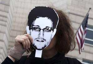 Mulher segura retrato de Edward Snowden, o ex-técnico da CIA que denunciou os sistemas de espionagem dos EUA Foto: THOMAS PETER / Reuters
