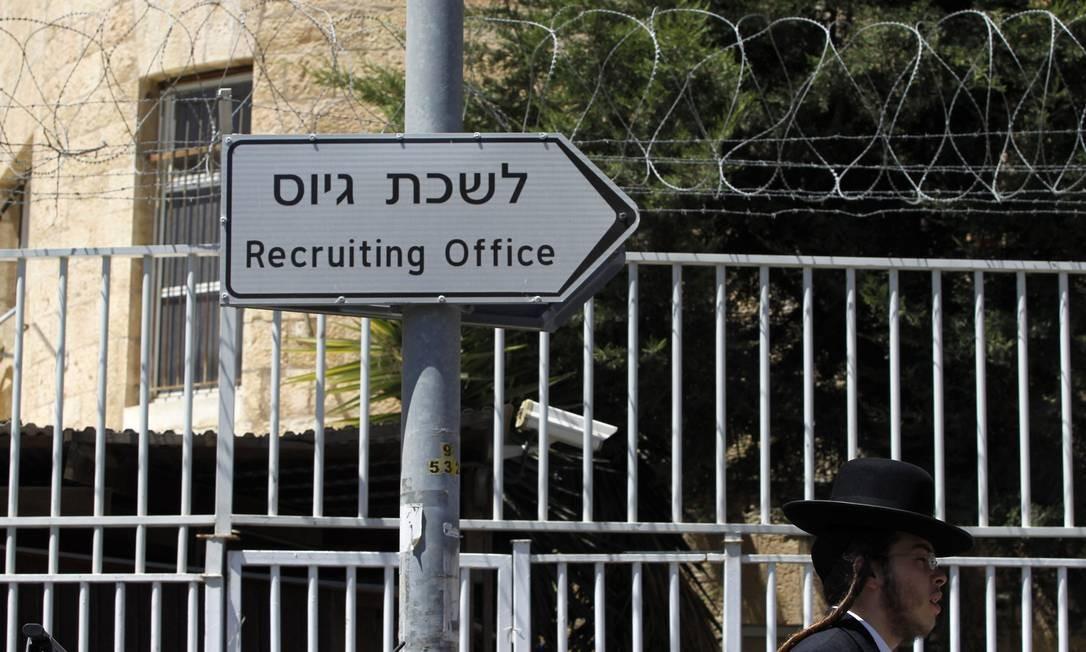 Um judeu ultra-ortodoxo passa em frente a entrada de um centro de recrutamento em Jerusalém Foto: Baz Ratner/Reuters
