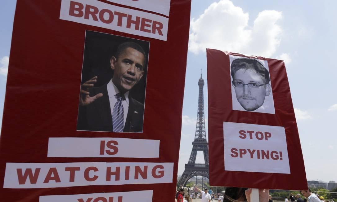 Manifestantes seguram cartazes com a foto de Barack Obama e do fugitivo americano Edward Snowden Foto: KENZO TRIBOUILLARD / AFP