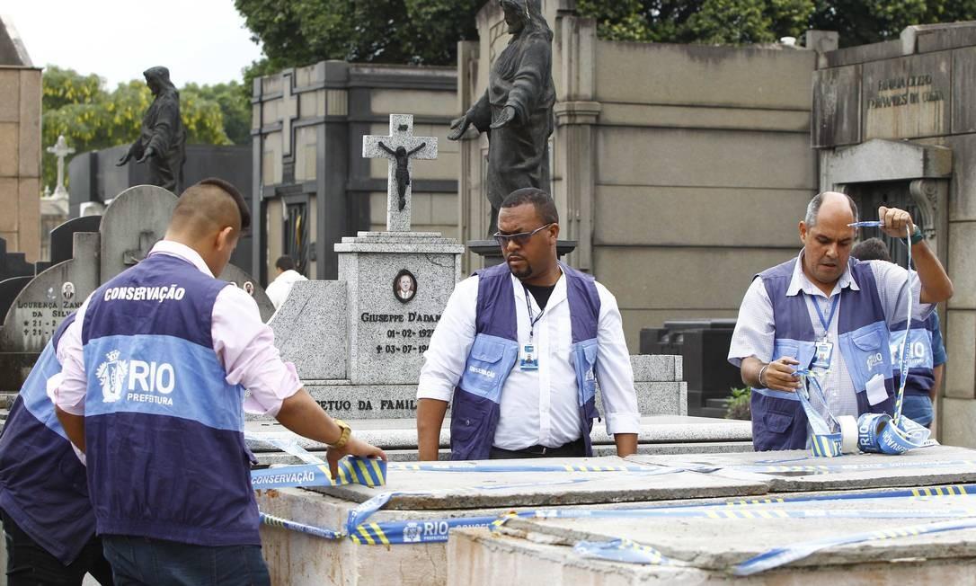 Agentes da prefeitura lacram jazigo pirata no Cemitério do Caju Foto: Pablo Jacob / O Globo