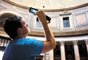 Aplicativos ajudam viajantes. Na foto, turista fotografa com seu smartphone Foto: Domenico Sinellis / AP