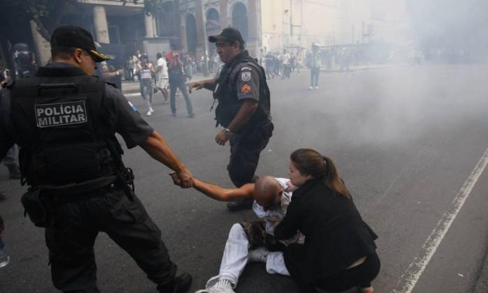 Policial ajuda manifestante ferido durante protesto perto da Candelária Marcelo Carnaval / Agência O Globo