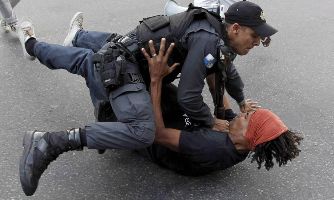 Policial tenta dominar um homem durante tumulto na Candelária Domingos Peixoto / Agência O Globo