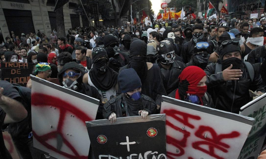 Um grupo usando máscaras se une aos manifestantes da passeata das centrais sindicais, no Rio Domingos Peixoto / Agência O Globo