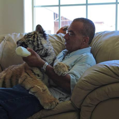 Um dos personagens do reality dá mamadeira a um tigre Foto: Divulgação