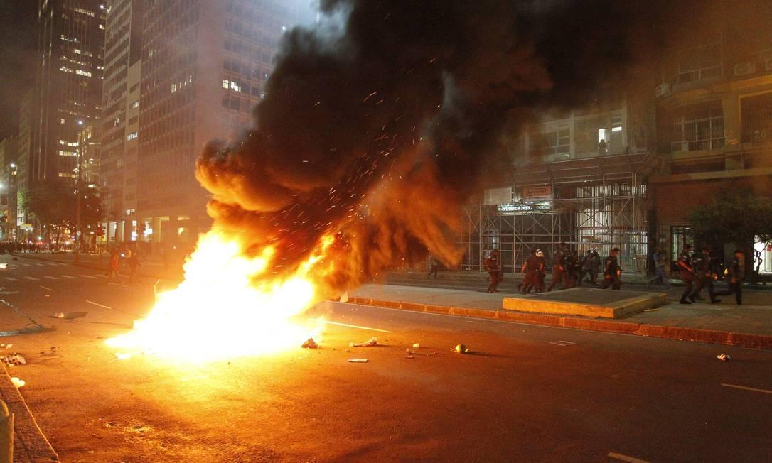 Policiais passam perto de fogueira acesa por manifestantes durante protesto no Centro do Rio Domingos Peixoto / O Globo