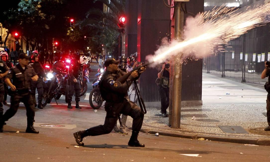 Policial reage a ação de vendalismo na Avenida Chile atirando bomba de gás lacrimogêneo Marcelo Piu / Agência O Globo