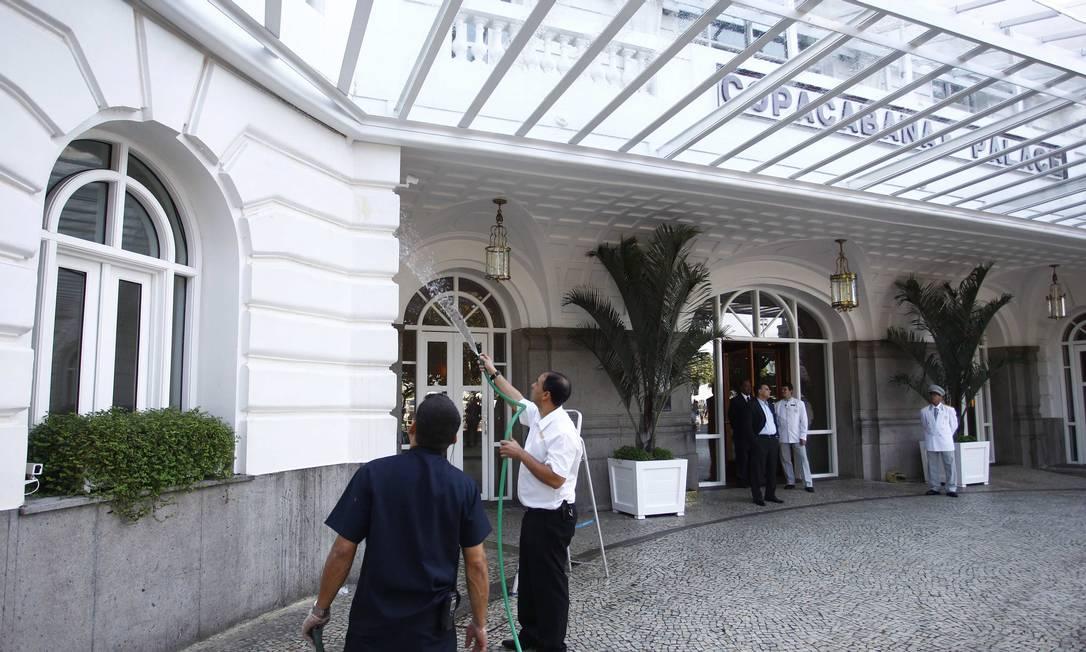 Funcionários limpam a fachada do Hotel Copacabana Palace, que foi palco de protesto durante a madrugada Foto: Pablo Jacob / Agência O Globo