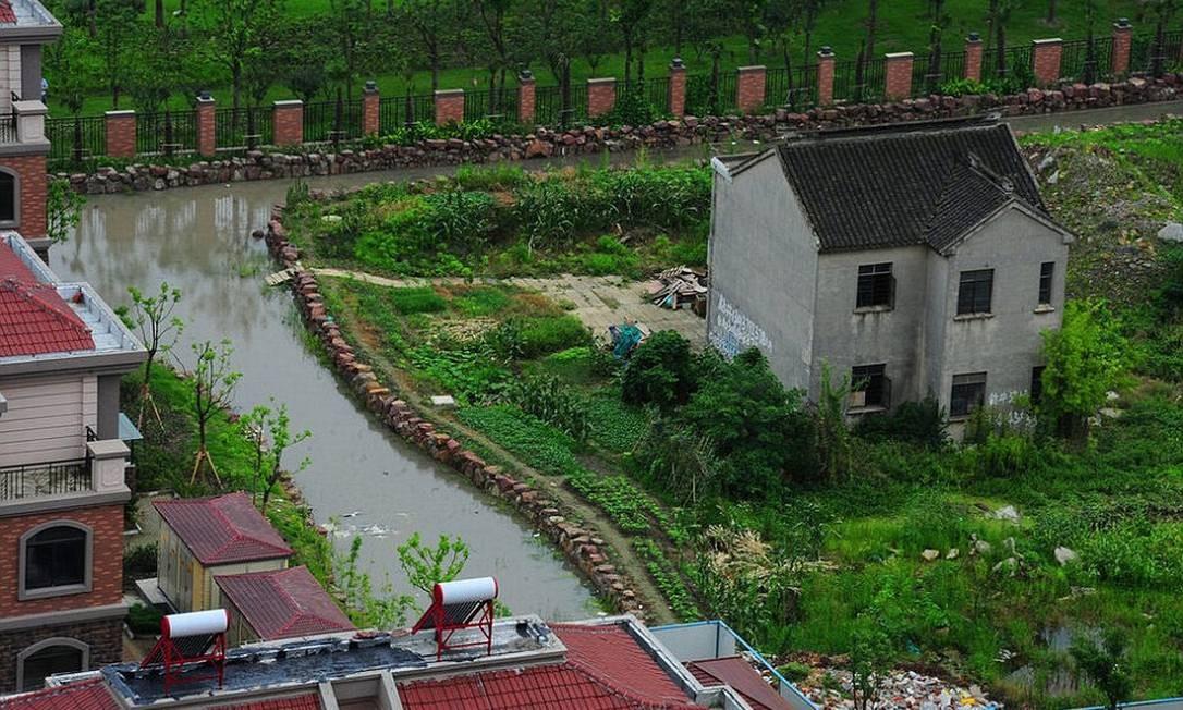 A casa do chinês de 75 anos foi cercada por um fosso d´água. Zhuang Longdi e sua família precisam atravessar um caminho com água até a cintura para chegar ao imóvel Foto: Daily Mail