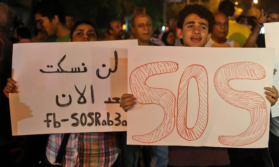 Manifestantes pró-Mursi seguram cartazes denunciando a perseguição política de islamistas Foto: Hussein Malla / AP