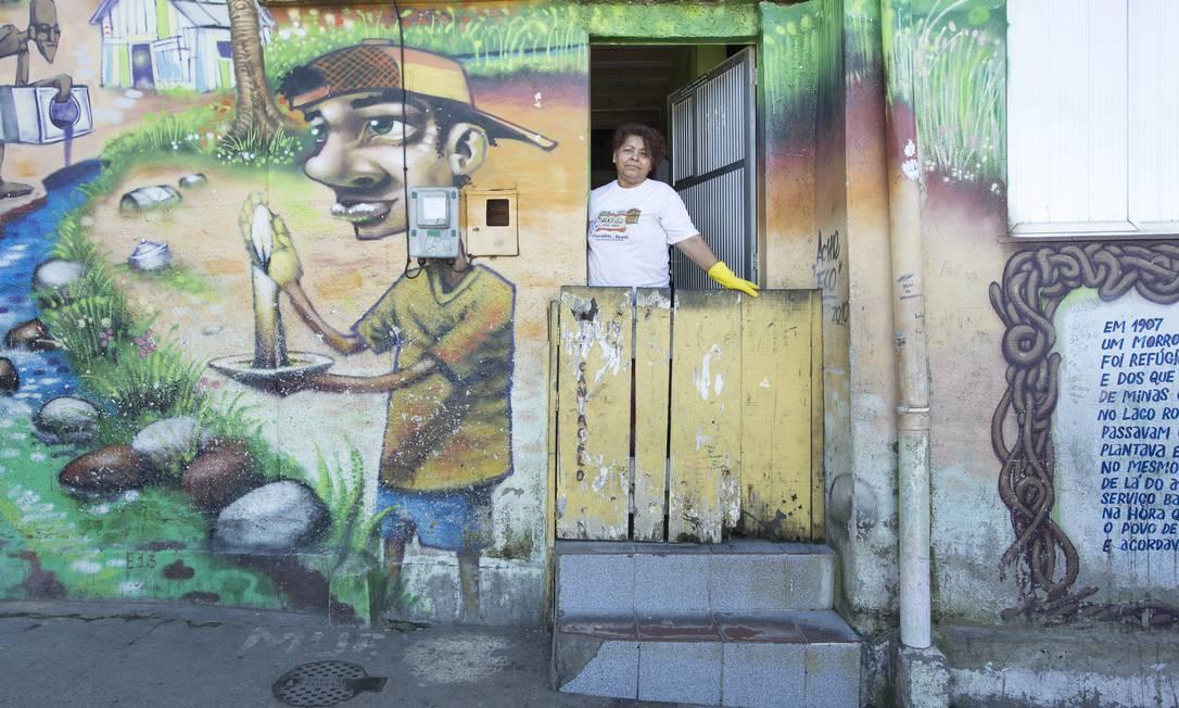 Na casa-tela de Regina Cabral, o grafite retrata os tempos em que a favela não tinha luz nem água, e a iluminação era à base de velas Foto: Leo Martins / O Globo