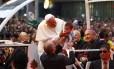 Observado pelo arcebispo do Rio, Dom Orani Tempesta, o Papa Francisco abençoa uma criança durante o desfile pelo Centro do Rio