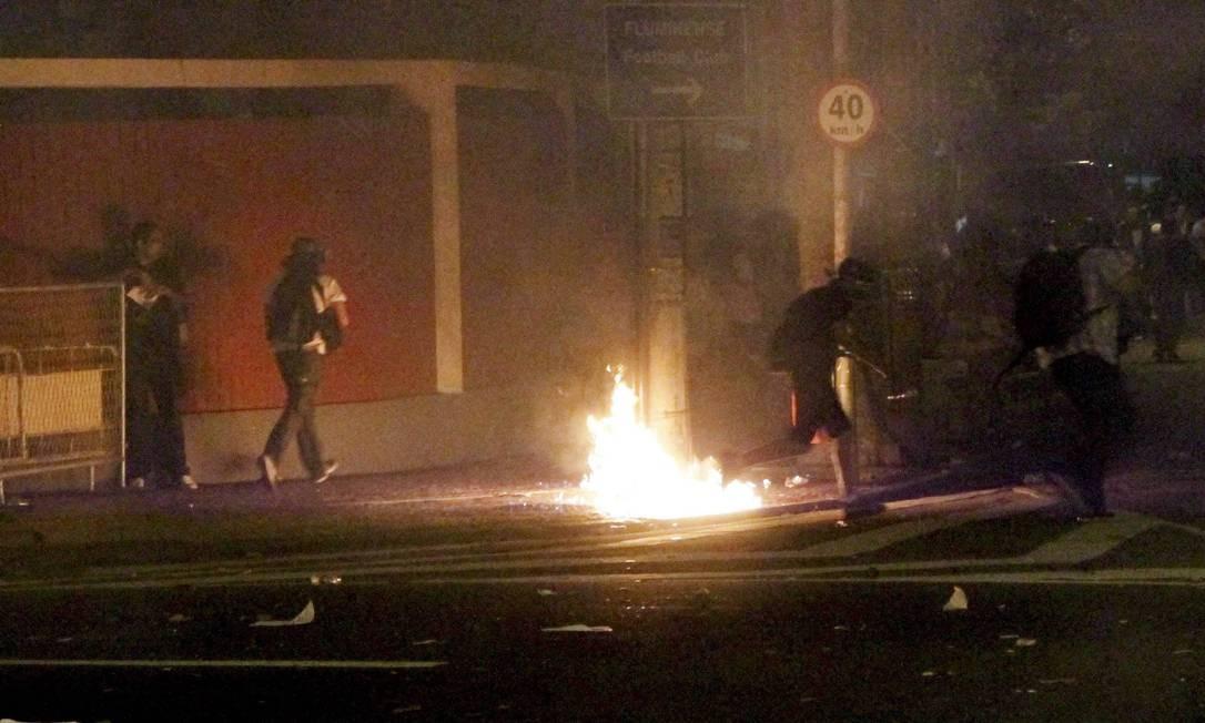 Com rostos cobertos, manifestantes colocam fogo em rua de Laranjeiras Foto: Marcelo Piu / O Globo