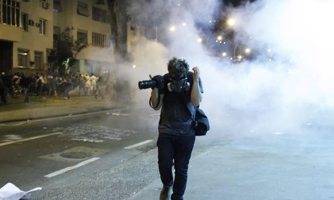Fotógrafo se protege de resquícios de bomba de efeito moral Foto: Marcelo Piu / Agência O Globo