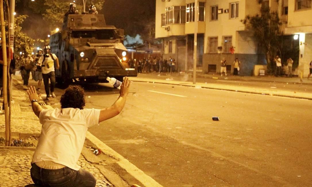 Manifestante, sentado na calçada, pede que policiais não avancem em Laranjeiras Foto: Marcelo Piu / O Globo