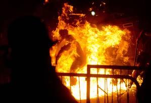 Um policial é atingido por coquetel molotov durante confrontos em Laranjeiras Foto: Victor R. Caivano / AP