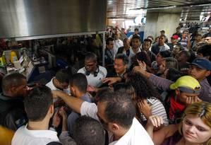Policial ajuda a conter tumulto na estação Uruguaiana do metrô na tarde de terça-feira Foto: Pedro Kirilos / Agência O Globo