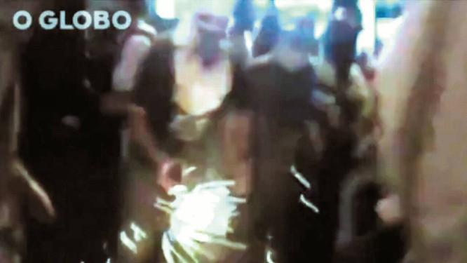 Um homem acende um coquetel molotov para lançar contra PMs durante protesto em Laranjeiras Foto: Reprodução/Vídeo da PM