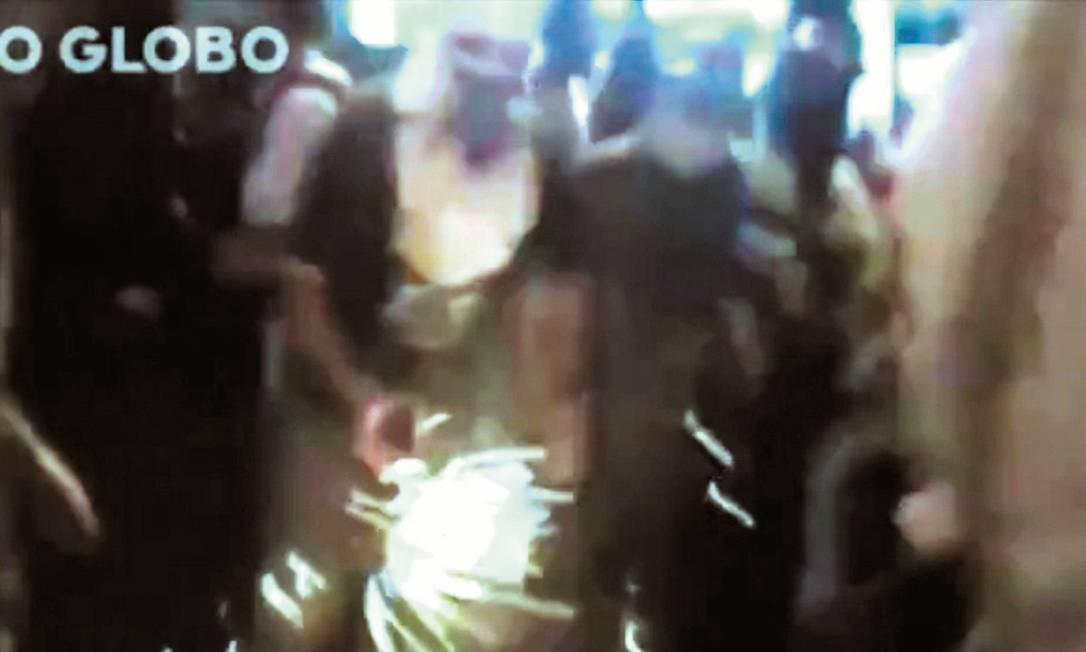 Um homem acende um coquetel molotov para lançar contra PMs durante protesto em Laranjeiras Foto: Terceiro / Reprodução/Vídeo da PM