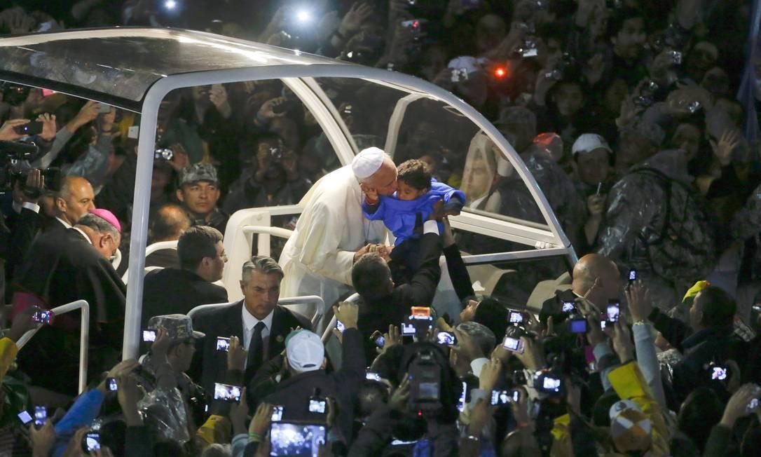 Papa beija uma criança a caminho do palco em Copacabana Guito Moreto / Agência O Globo