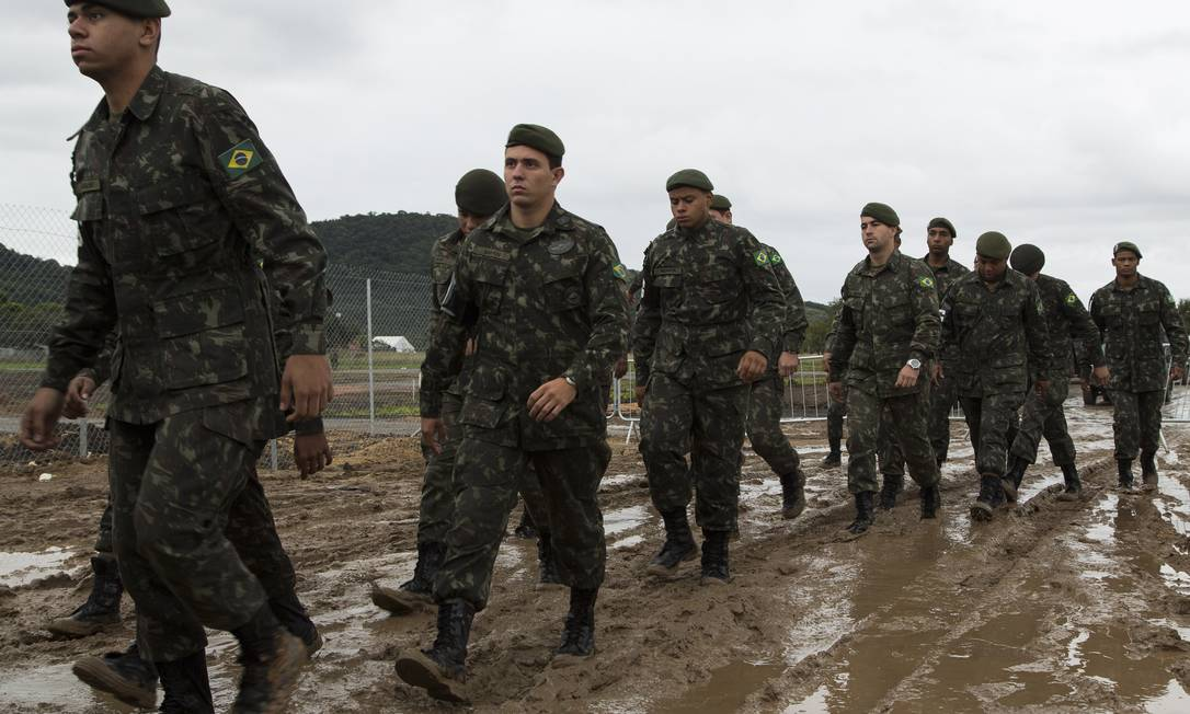 Militares caminham sobre a lama do Campus Fidei, em Guaratiba Foto: Leo Martins / Agência O Globo