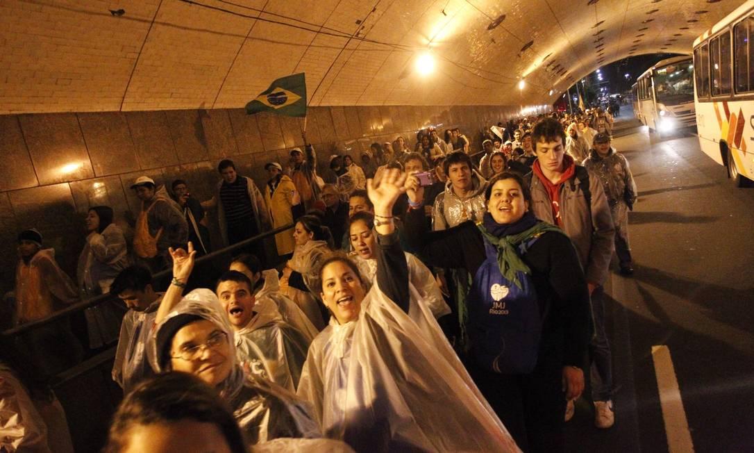 Peregrinos acenam enquanto atravessam túnel em Copacabana Pedro Kirilos / Agência O Globo