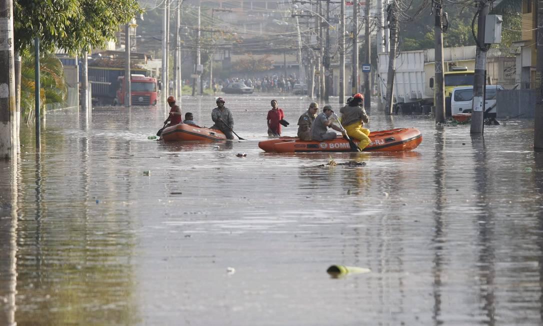 Bombeiros usam botes para chegar às casa Pablo Jacob / Agência O Globo