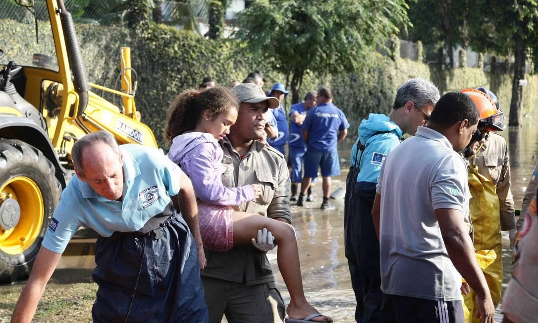 Bombeiro ajuda criança a sair da região alagada Thiago Lontra / Agência O Globo