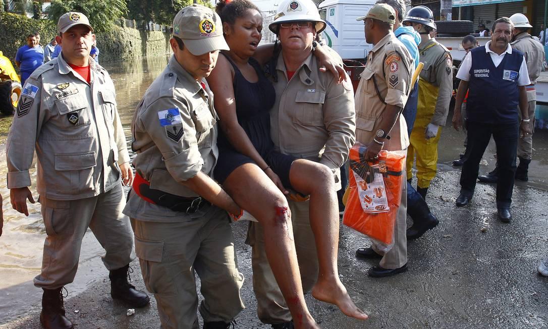 Bombeiros carregam mulher que se feriu após rompimento da adutora Pablo Jacob / Agência O Globo