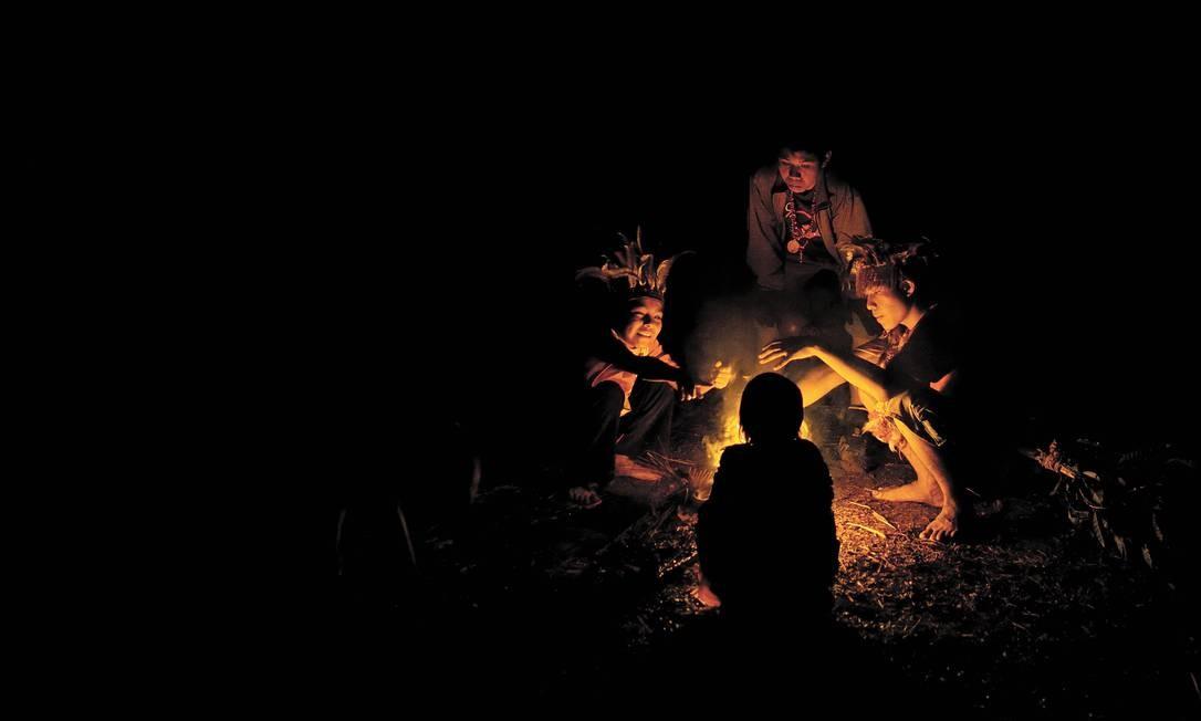 Jovens índios guarani ficam em volta de uma fogueira em Aral Moreira, no Mato Grosso do Sul Foto: Maurício Lima/New York Times