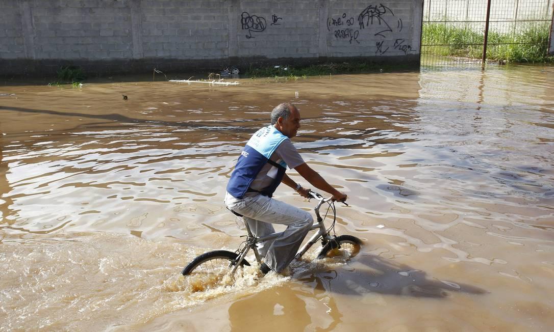 Homem pedala pela rua alagada Pablo Jacob / Agência O Globo