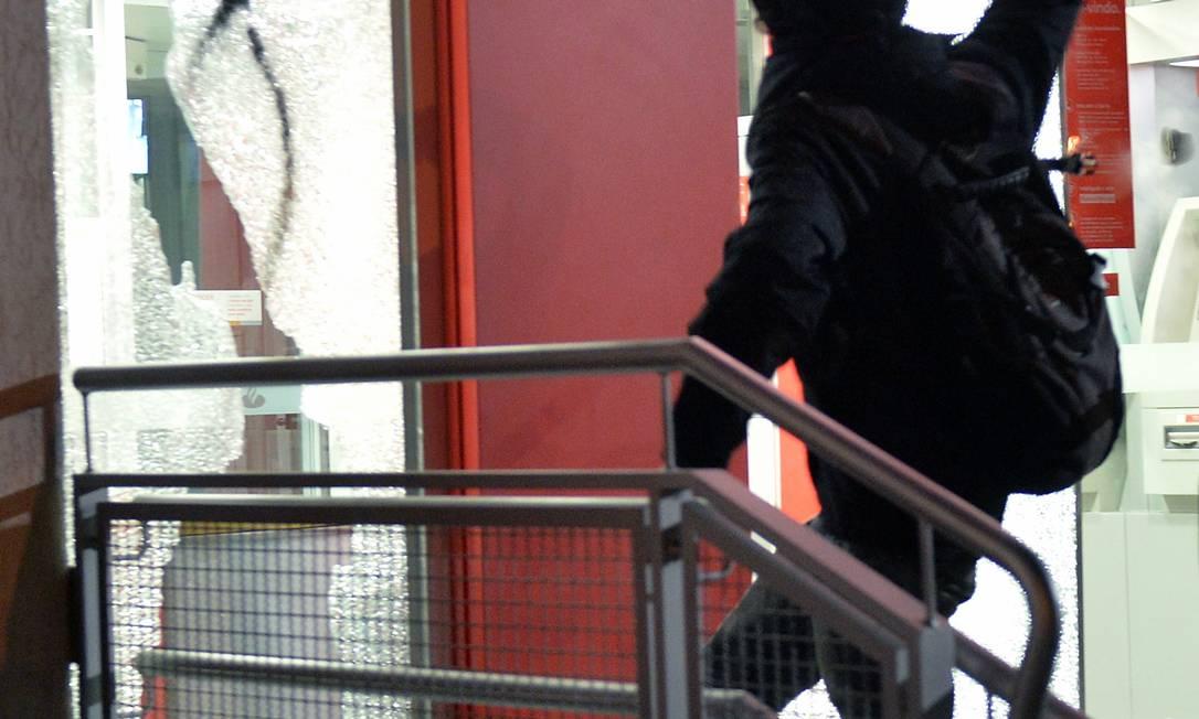 Jovem quebra vidraça de agência bancária Foto: AFP