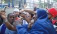 Coberto por uma toalha azul, o sorridente Phil Davis faz fotos com os fãs brasileiros no Circo Voador
