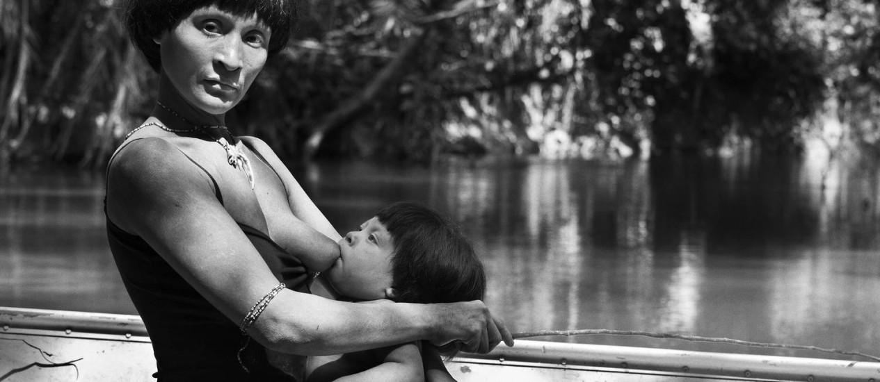 Índia Awá amamenta seu filho recém-nascido enquanto pesca no rio Caru Foto: © Sebastião Salgado/Amazonas Images / O Globo