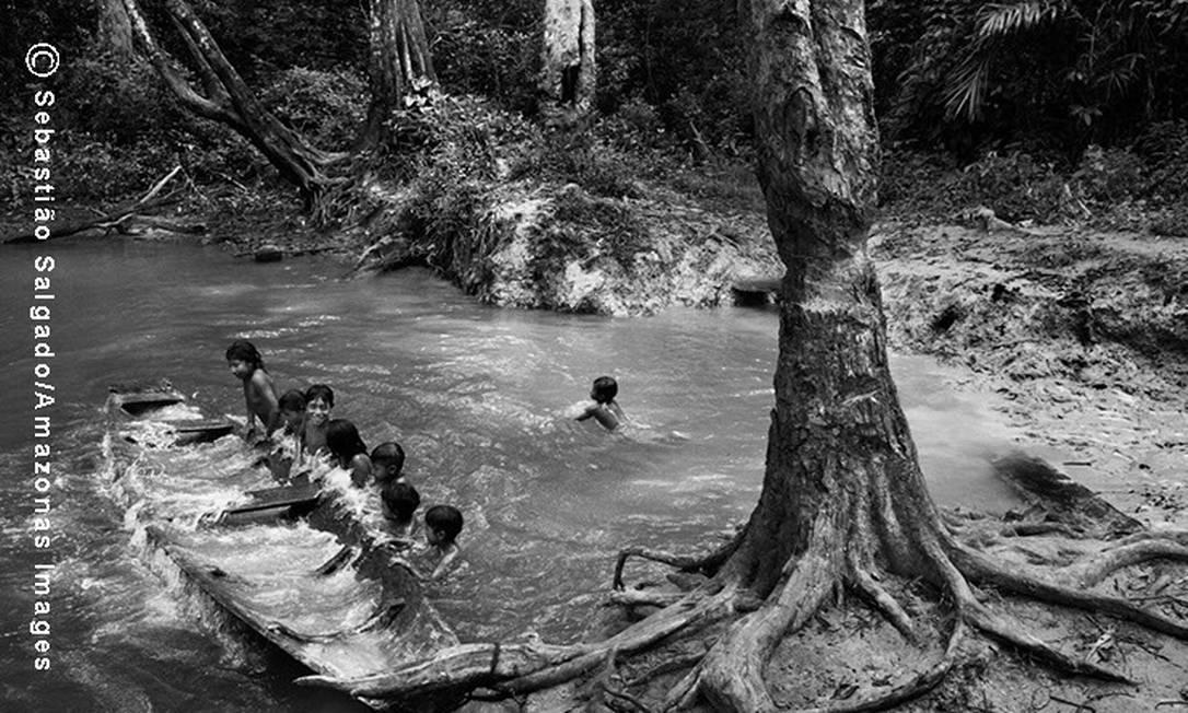 Crianças Awá esvaziam uma canoa para tentar se equilibrar durante um banho de rio