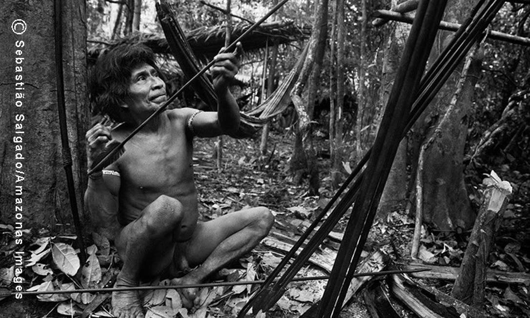 Antes de sair à caça, ao amanhecer, o índio Muturuhum aquece suas flechas para alinhá-las