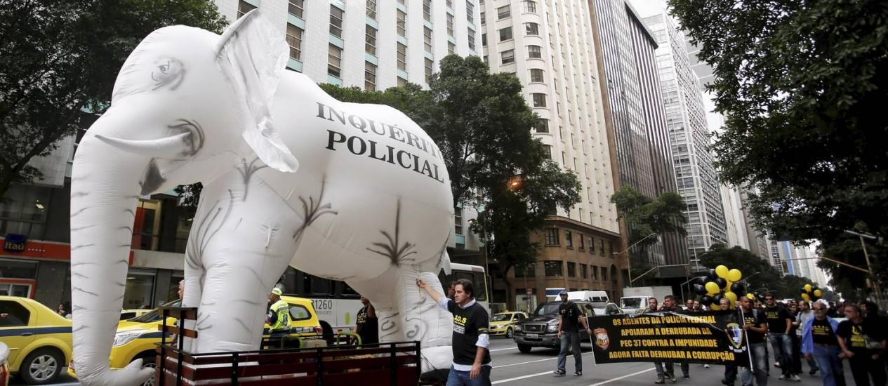 Grande elefante branco inflável é carregado pelos policiais federais durante manifestação no Centro do Rio Foto: Hudson Pontes / Agência O Globo
