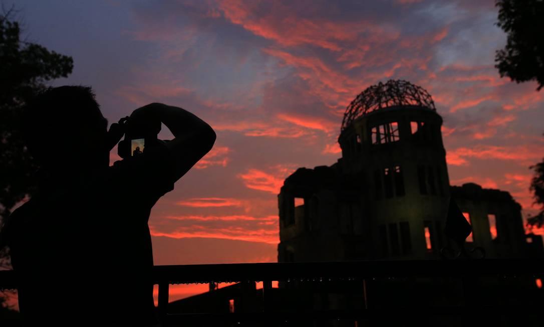 Homem fotografa o monumento em lembrança à bomba atômica lançada sobre Hiroshima, no Japão Shizuo Kambayashi / AP